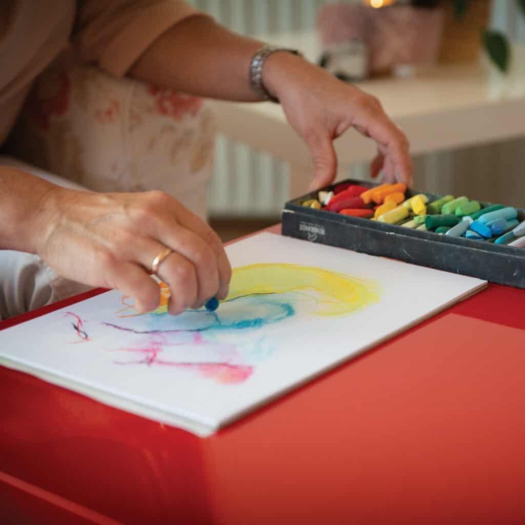 Tegning med kulkridt farver ned på papiret